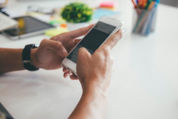 Zbliżenie ręka używać telefon komórkowego.