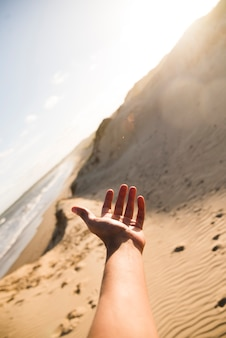 Zbliżenie ręka wskazuje przy plaża krajobrazem