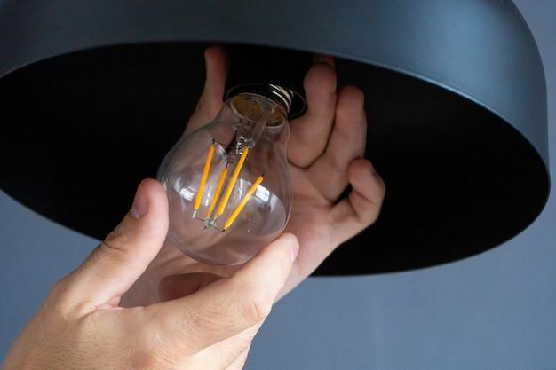 Zbliżenie. ręka zmienia żarówkę w stylową lampę na poddaszu. żarówka spiralna. nowoczesne wnętrze.