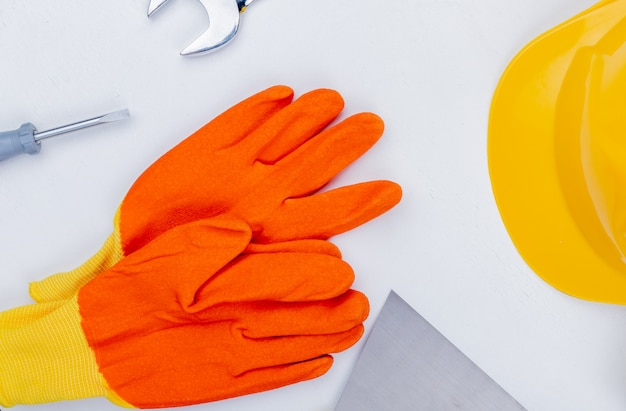 Zbliżenie rękawic z kluczem do kasku i śrubokrętem na białym tle