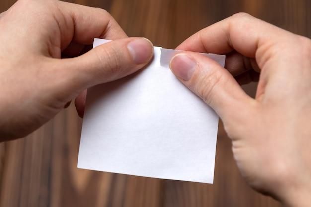 Zbliżenie ręki drzeje pustego prześcieradło papier. makieta