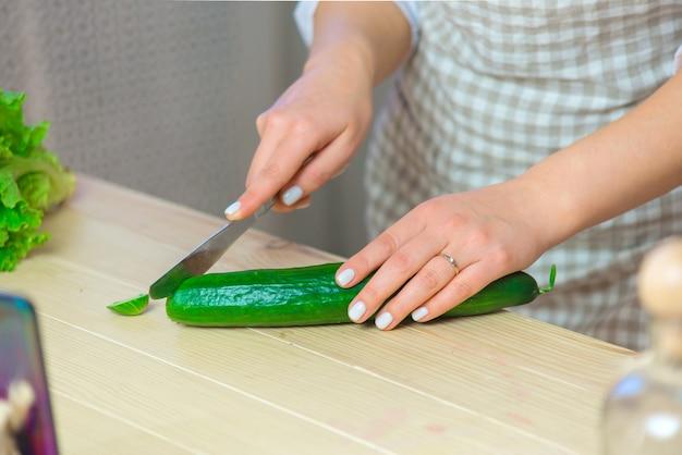 Zbliżenie ręki kobiety siekanie warzyw z nożem w kuchni