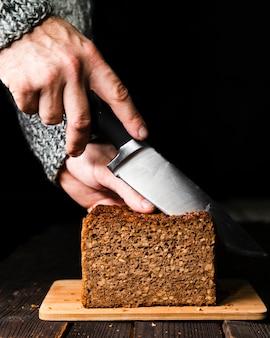Zbliżenie ręki krojenia chleba domowej roboty