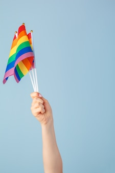 Zbliżenie ręki macha małą tęczową flagę na jasnoniebieskim tle