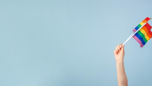 Zbliżenie ręki macha małą tęczową flagę na jasnoniebieskim