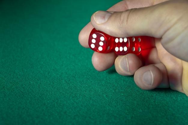 Zbliżenie ręki mienia czerwoni kostka do gry z wygraną kombinacją na zielonym płótnie w kasynie.