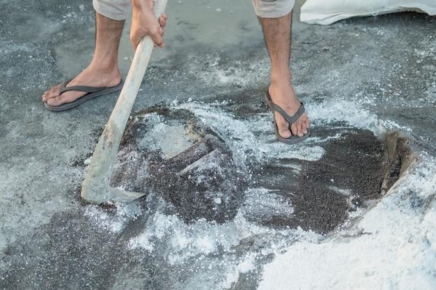 Zbliżenie ręki murarza trzymającego motykę do ciasta na piasek i cement dla budynków