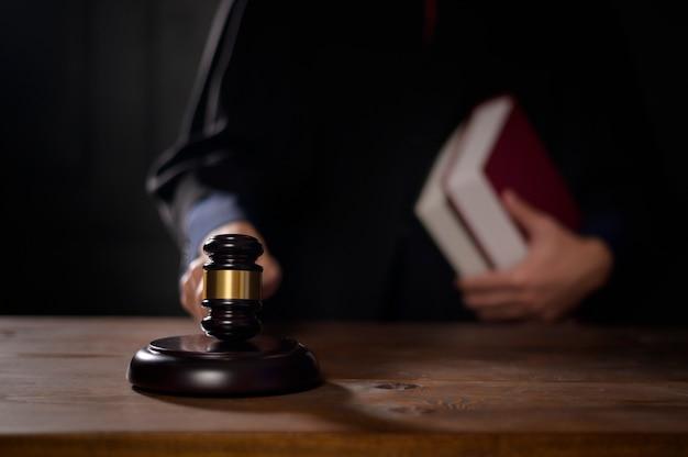 Zbliżenie ręki sędziego uderza młotkiem sędziego w sądzie