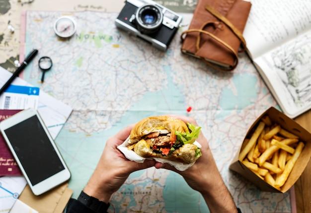 Zbliżenie ręki trzyma hamburger nad mapy tłem