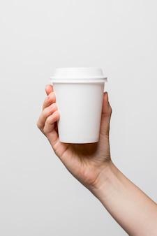 Zbliżenie ręki trzymającej biały kubek
