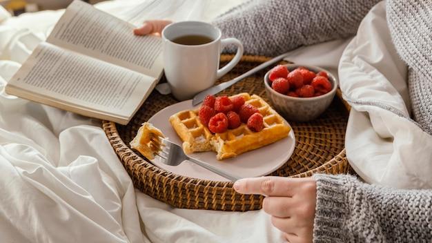 Zbliżenie ręki trzymającej książkę i widelec