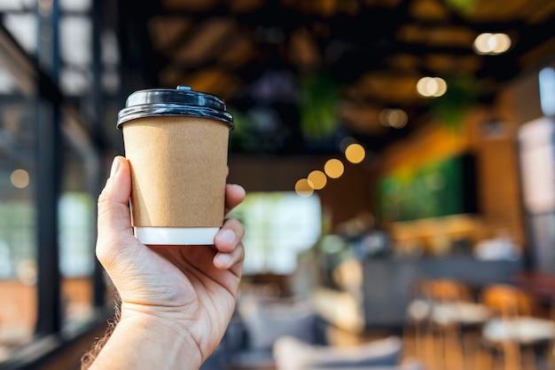 Zbliżenie ręki trzymającej papierowy kubek kawy w kawiarni