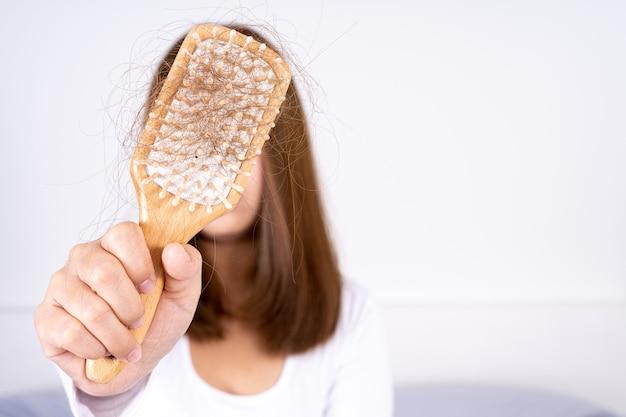 Zbliżenie ręki trzymającej problem z opadaniem grzebienia i włosów.