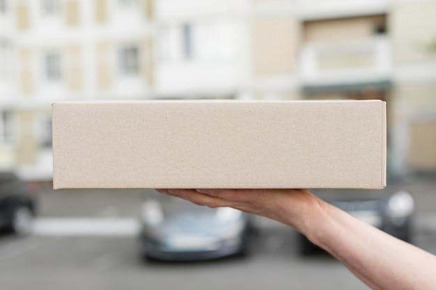 Zbliżenie ręki trzymającej pudełko