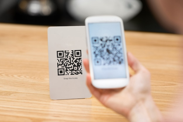 Zbliżenie ręki trzymającej telefon i skanowanie kodu qr