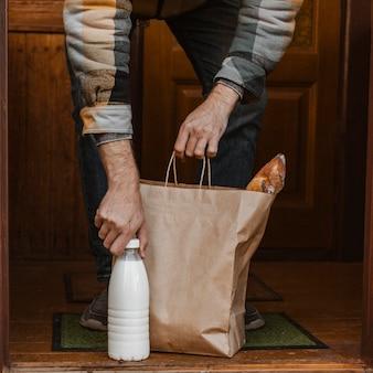 Zbliżenie ręki trzymającej torbę i butelkę mleka