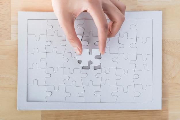 Zbliżenie ręki umieszczającej ostatni element układanki, ręka trzymająca brakujący element układanki na to miejsce