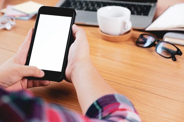 Zbliżenie ręki używać smartphone przy biurowym biurkiem.