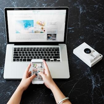 Zbliżenie ręki używać telefonu komórkowego i komputeru laptop na czerń marmuru stole