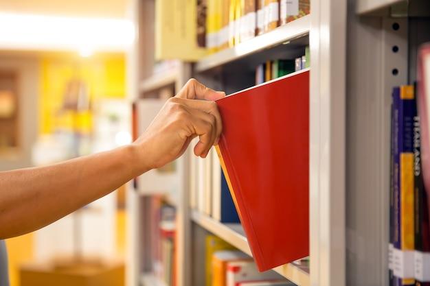 Zbliżenie ręki wybierając książkę z półki.
