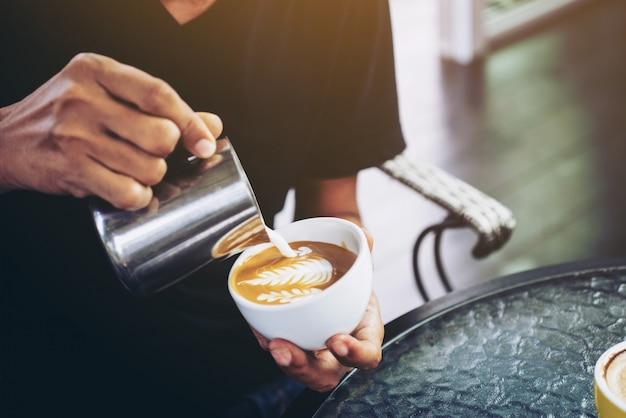 Zbliżenie robi latte sztuki ostrości w mleku i kawie w rocznika kolorze barista selekcyjna ostrość