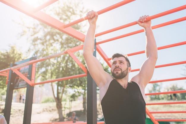 Zbliżenie robi silnego sportowca pull-up na drążku. mężczyzna fitness z błękitne niebo w ścianie i otwartej przestrzeni wokół niego. młody człowiek z sportive ubrania w mieście.