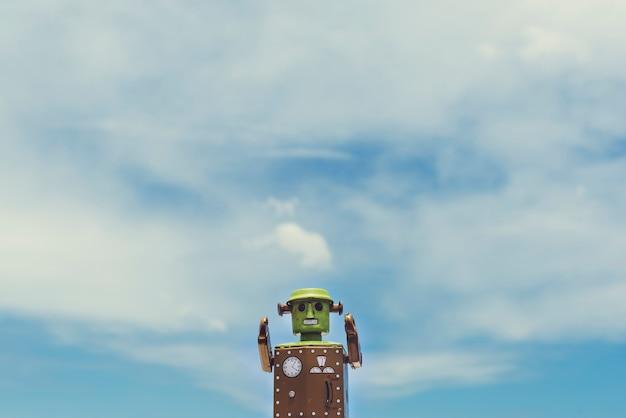 Zbliżenie robot zabawka z chmurnym niebieskim niebem scenicznym