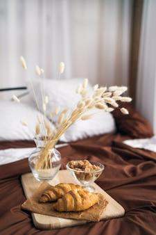 Zbliżenie: rogaliki, brązowy cukier i suszone kwiaty w wazonie stoją na drewnianej desce w białym łóżku z brązową narzutą. zdjęcie wysokiej jakości