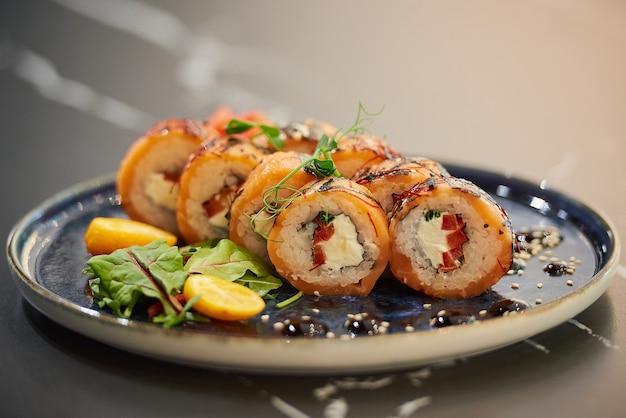 Zbliżenie rolek sushi z łososiem, serem philadelphia i tuńczykiem na niebieskim talerzu ceramicznym z sosem, sezamem, płatkami kumkwatu i liśćmi. stół z czarnego kamienia.