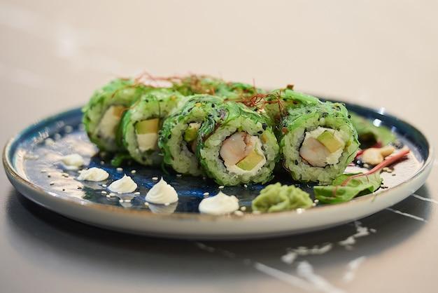 Zbliżenie rolek sushi z wodorostami chuka wakame, serem philadelphia i krewetkami na niebieskim talerzu ceramicznym z sosem, orzechami nerkowca i wasabi na czarnym kamiennym stole.