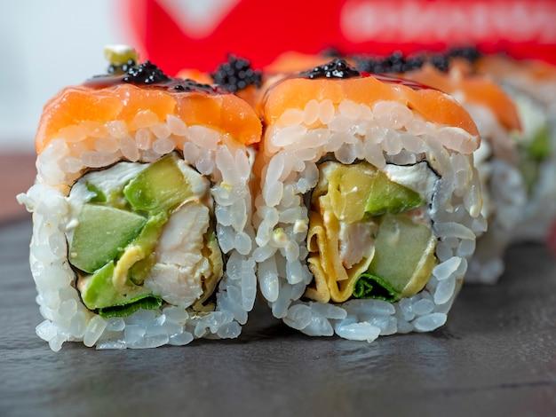 Zbliżenie rolki sushi na czarnej płycie. tradycyjna kuchnia japońska