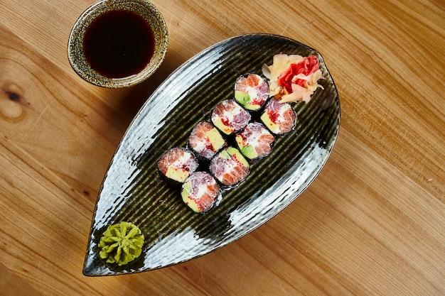 Zbliżenie rolki sushi z maki z tuńczykiem i łososiem, twarogiem, kawiorem tobiko na czarnym talerzu z sosem sojowym