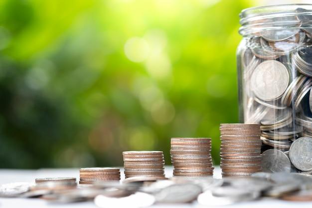 Zbliżenie rośnie monety układania z tłem zieleni i światło słoneczne.