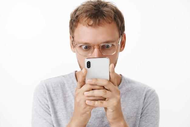 Zbliżenie rozbawionego męskiego maniaka w okularach trzymającego smartfon blisko twarzy wyskakujące oczy i wpatrującego się zaintrygowany w ekran urządzenia czytającego szokującą interesującą wiadomość na białej ścianie