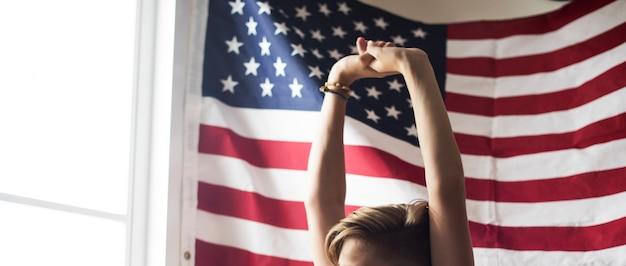 Zbliżenie rozciąganie ręki z flaga amerykańską tłem