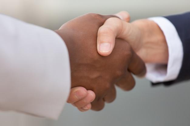 Zbliżenie różnorodny biznesowy kolegi uścisk dłoni