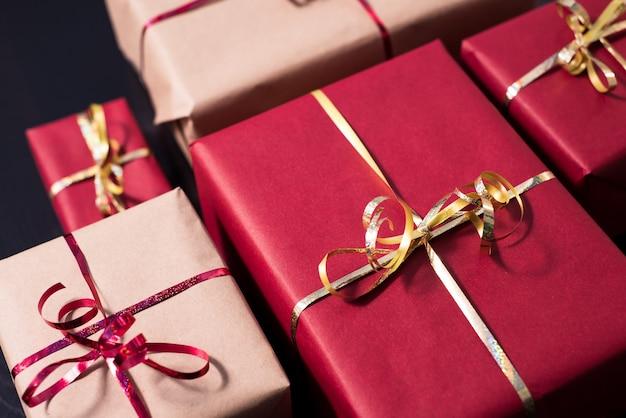 Zbliżenie różnych prezentów owiniętych w kolory czerwony i kraft z ozdobnymi wstążkami