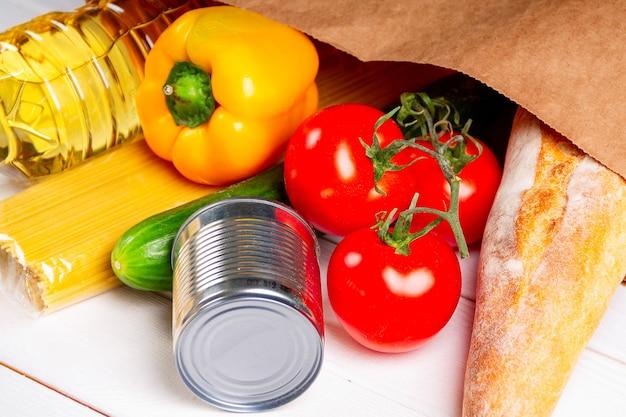 Zbliżenie różnych zdrowej żywności, pomidorów, chleba, makaronu w papierowej torbie na białym tle. dostawa jedzenia