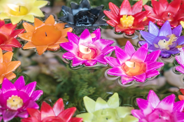 Zbliżenie różowa świeczka w kwiatu kształcie na zamazanej kolorowej kwiat świeczce unosi się na wodzie textured tło