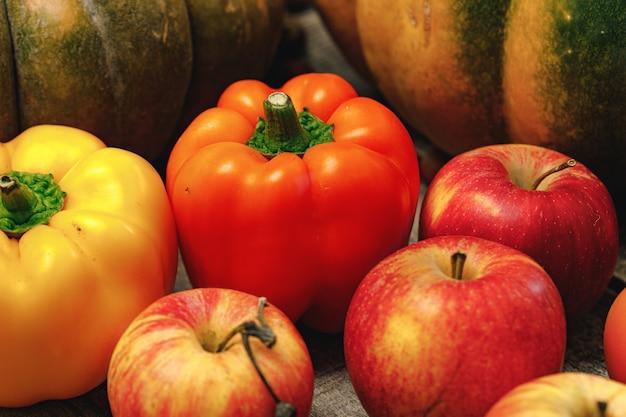 Zbliżenie rozproszonych warzyw dyni, pieprzu i jabłek
