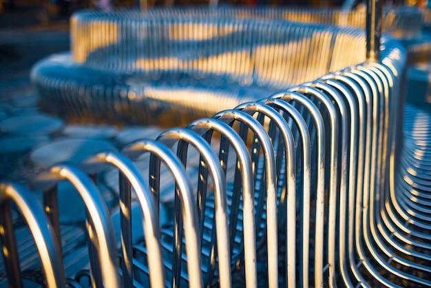 Zbliżenie rur metalowych ławek ulicznych ułożonych równolegle do siebie na strukturze ulicy. koncepcja materiałów odpornych na warunki atmosferyczne i nowoczesnego wzornictwa przemysłowego.