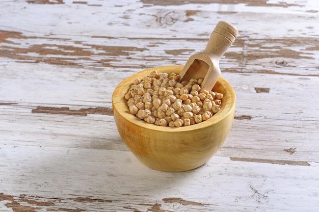 Zbliżenie rustykalnej drewnianej miski surowej ciecierzycy (cicer arietinum)