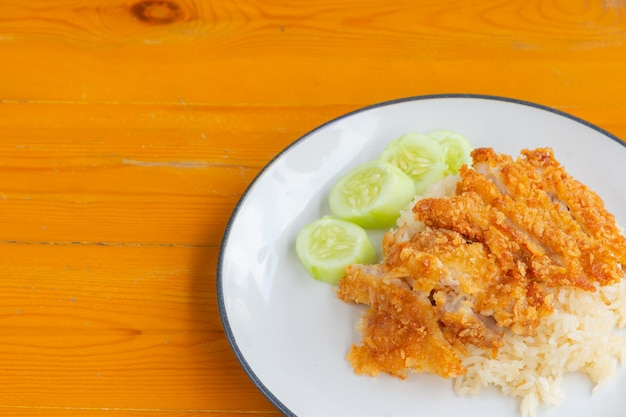 Zbliżenie ryżu smażonego kurczaka z ogórkiem na drewnianym stole