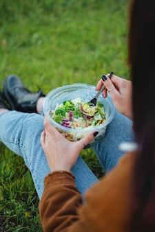 Zbliżenie salaterki na nogach nastolatki siedzi na trawie, ciesząc się przyrodą pionowe ujęcie
