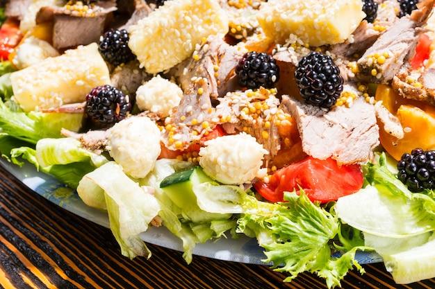 Zbliżenie sałatka dla smakoszy ze świeżych owoców i warzyw, wybór serów i mięs na rustykalnym drewnianym stole