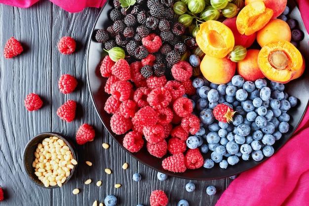 Zbliżenie: sałatka z owoców i jagód z agrestem, malinami czerwonymi i czarnymi, jagodami, plasterkami moreli na czarnym talerzu na drewnianym stole z orzeszkami pinii, widok poziomy z góry, układanie płaskie