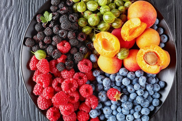 Zbliżenie: sałatka z owoców i jagód ze świeżego organicznego agrestu, maliny czerwonej i czarnej, borówki, plasterków moreli na czarnym talerzu na drewnianym stole, widok poziomy z góry, układanie płaskie