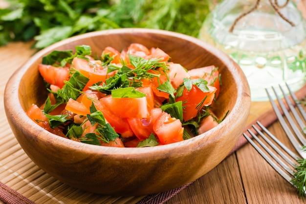 Zbliżenie: sałatka z pomidorów i świeżych ziół, oleju roślinnego i widelca na drewnianym stole