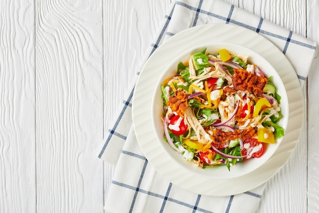 Zbliżenie sałatki z kurczaka ze smażonym boczkiem, sałatą rzymską, tartą piersią z kurczaka, serem cheddar, pomidorami i dressingiem jogurtowym w białej misce na drewnianym stole, układanie na płasko, wolne miejsce