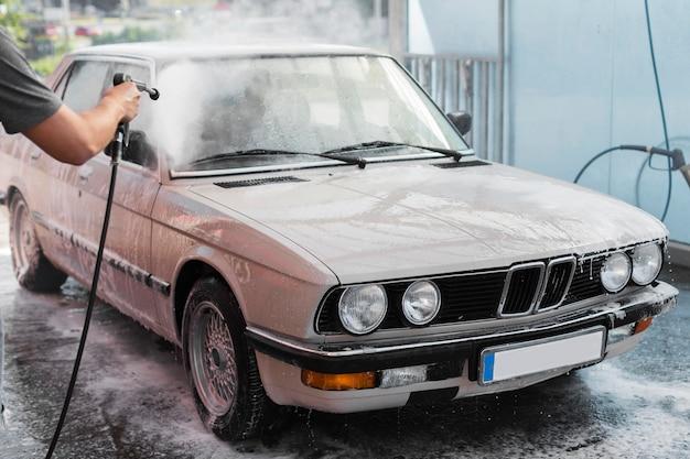 Zbliżenie samochodu do mycia rąk z wężem